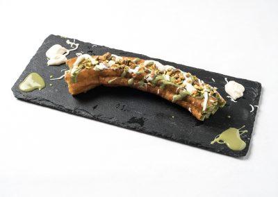 TAPA POSTRE: CHURRO RELLENO Con crema pastelera, crema de avellana y decorado con pistacho.
